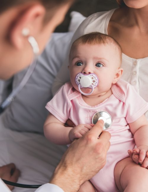 Beautiful young mom is holding her cute baby while doctor is listening to baby's lungs